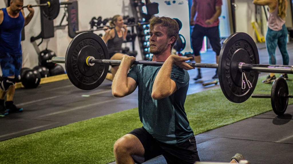 man doing a weighted front squat with a barbell