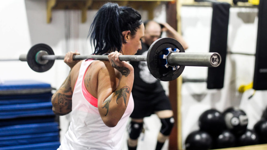 woman holding a barbell behind her head