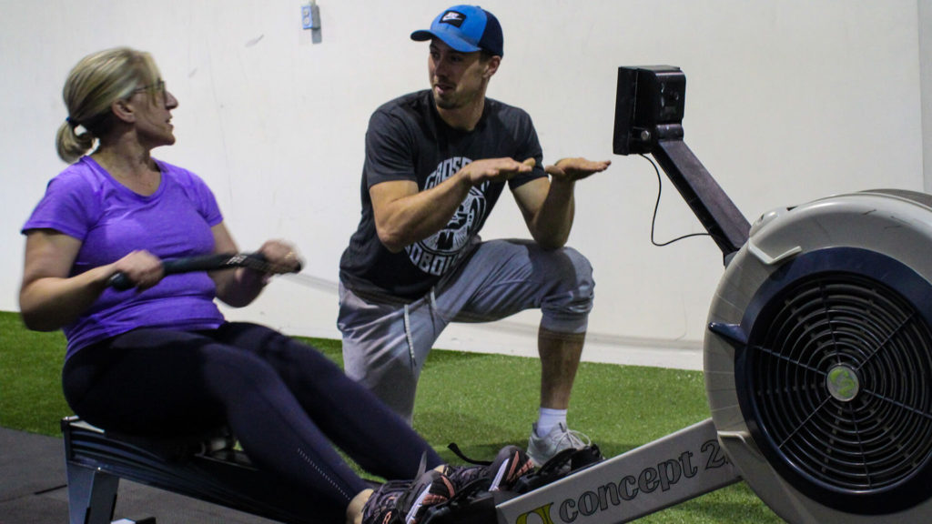 crossfit coach giving rowing instructions