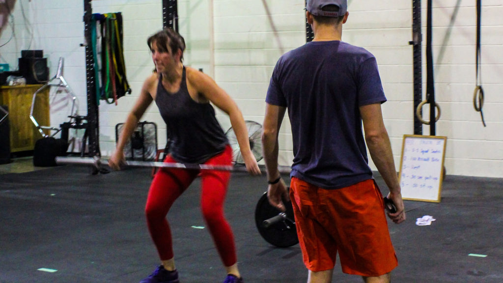crossfit coach evaluating woman doing a clean